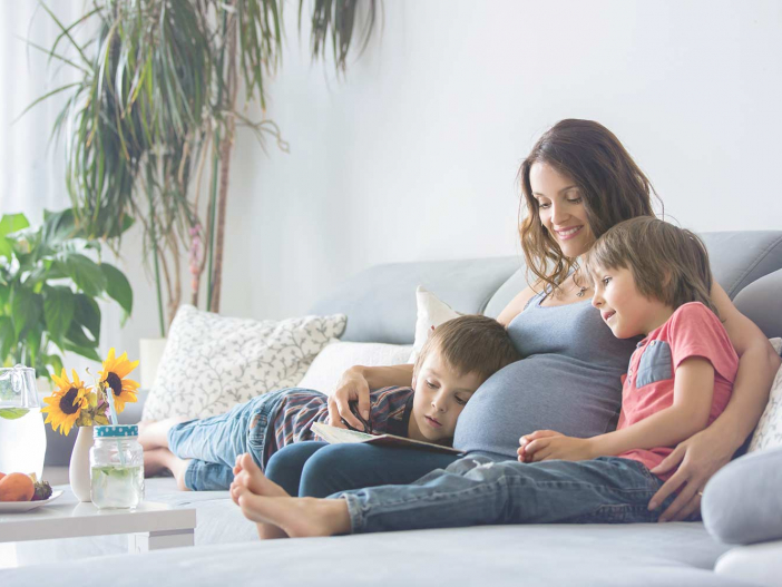 Surrogate mother with two children snuggling on the couch